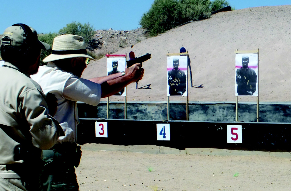 The late Mike Hughes from Gunsite looks over my shoulder while I run the Custom 14/45.