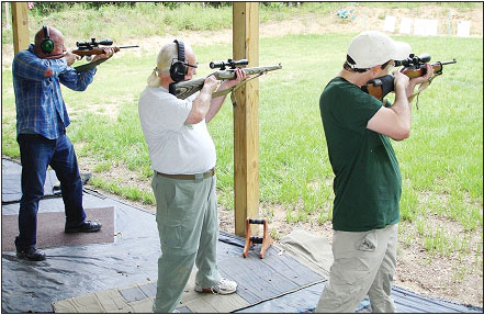 All three shooters at this range are using different types of Ruger 10/22 rifles, all with different aftermarket additions. One, at center, is a nice International variant, stocked to the muzzle.
