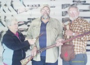 Judy and Anson Morgan present Jim Fulmer (center) his prizes from Michigan State Muzzleloaders annual give-a-way.