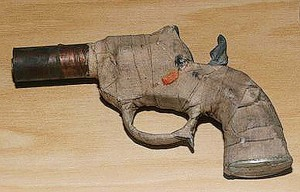 (Connecticut State) An interesting design, this .22 caliber zip gun, built by two high school boys, was seized during an attempt to smuggle it to a relative housed in a CT state prison. It is a cap gun with a pipe barrel, strong rubber band to power the striker and bound with medical tape.