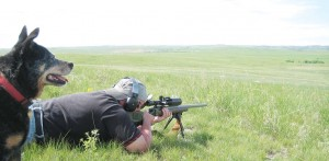 The author's buddy Jim K. reaching out on the prairie as the author's Heeler dog, Maggie, does the spotting.