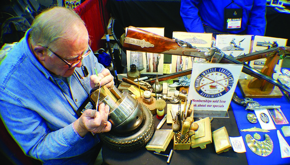 Master Engraver John Schippers demonstrating engraving at the NMLRA booth at the NRA convention.