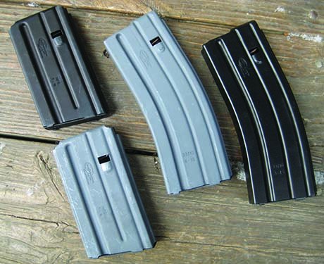 The grey magazines are the traditional military hard surface anodized finish with the Mil-Spec dry lube finish. The black mags have the PTFE finish.