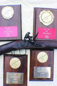 Author's new .32 cal. rifle with old trophies won when he was State Team Captain.