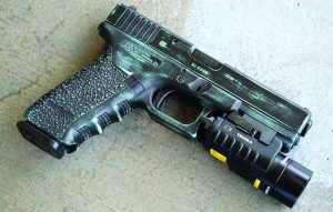The author deploys a TruGlo TruPoint combination light/laser with the Glock Model 22C.
