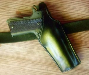 A close-up of El Paso Saddlery's #2 police duty crossdraw holster on a belt showing it's position for a fast draw.