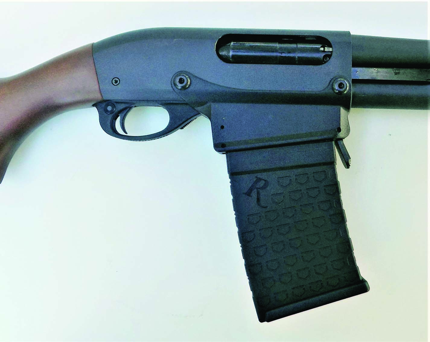 Remington's magazine fed 870DM proved reliable in action. Note receiver modifications.